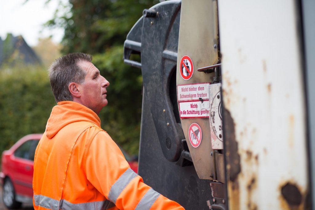Müllmann mit Müllcontainer am Müllauto