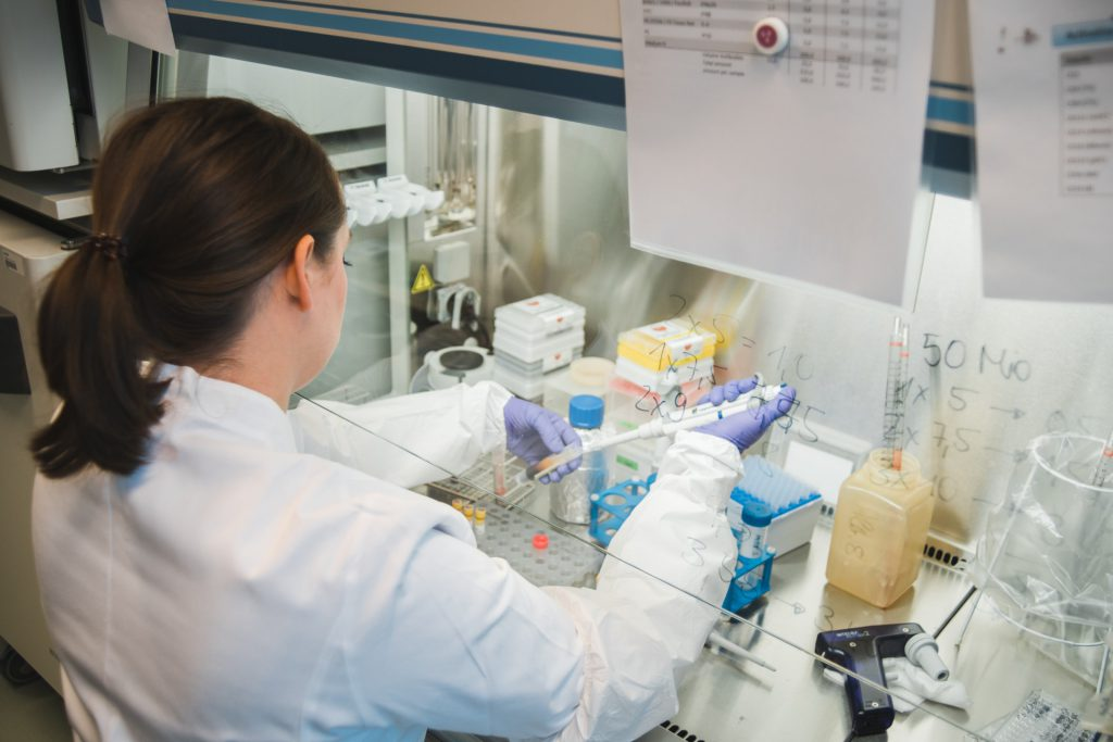 hiv forscherin im weißen Kittel arbeitet mit Proben