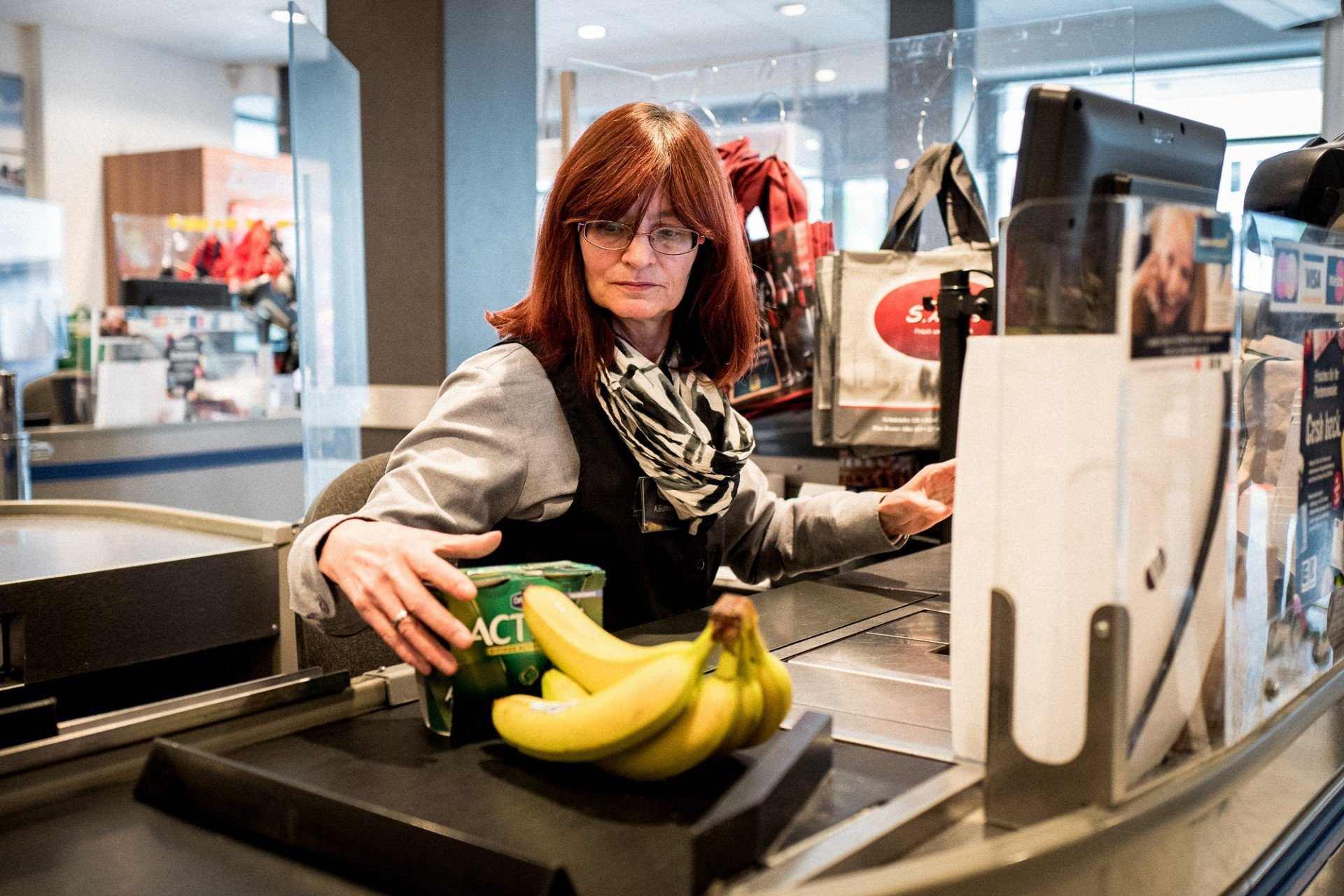 Kassiererin zieht Bananen und Joghurt über das Band.