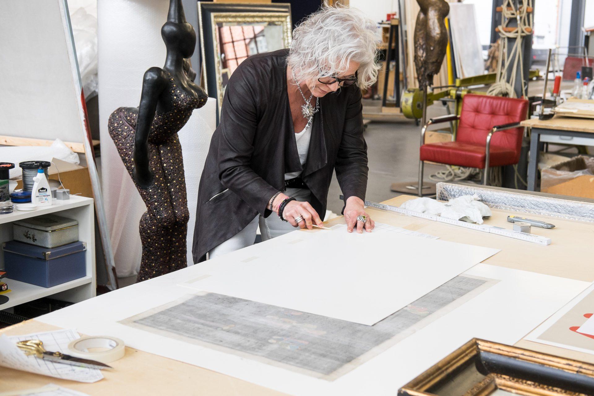 Rahmenkünstlerin am Tisch stehend und rahmt ein Bild