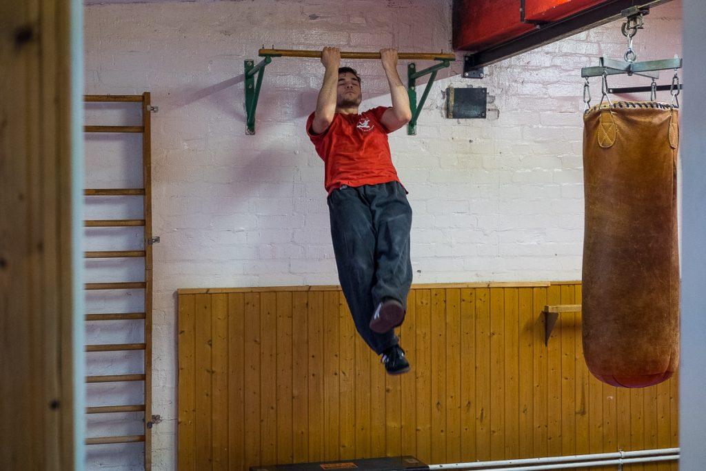 Kung Fu Schüler macht Klimmzüge an einer Stange_40Stunden