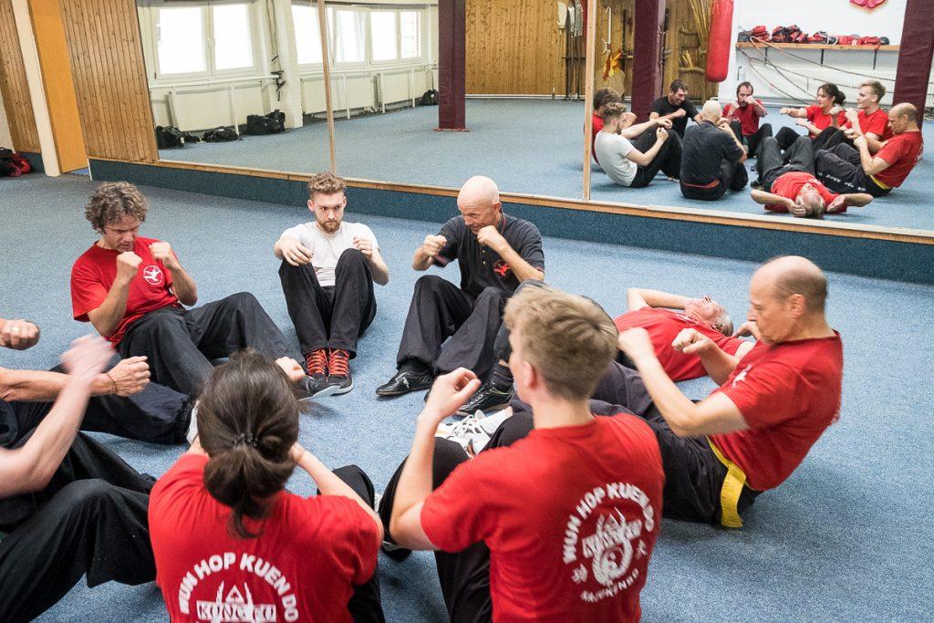 Gruppe von Schülern sitzt im Kreis auf dem Boden und machen Situps_40Stunden