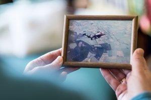 Die Philosophin hält ein gerahmtes Foto einer Fallschirmspringerin in der Hand.