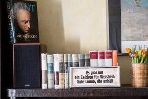 """Vor zahlreichen Büchern steht ein Schild mit der Aufschrift """"Es gibt nur ein Zeichen für Weisheit: Gute Laune, die anhält."""""""