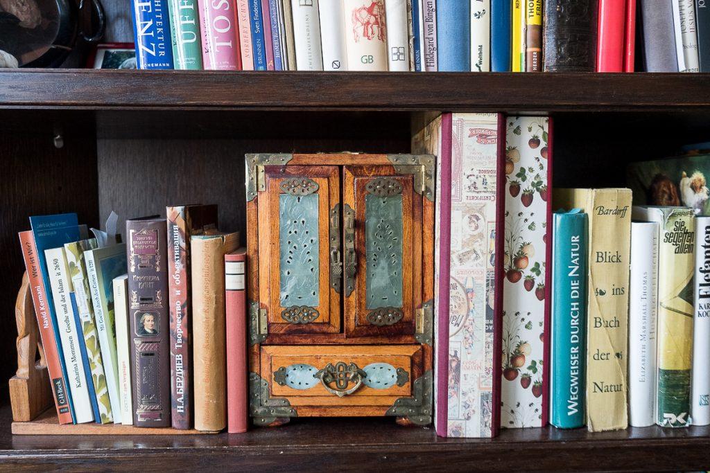 In einem Bücherregal steht eine kleine Truhe.