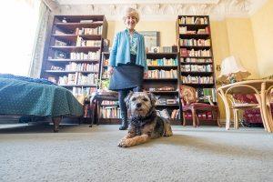 Die Philosophin mit ihrem Hund vor dem großen Bücherregal.
